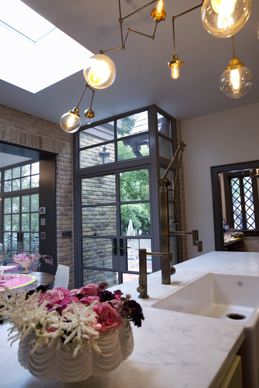A kitchen with custom copper lights, a white marble countertop, a Rohl farmers sink, steel and glass doors and windows, a brick wall, and pink flowers.