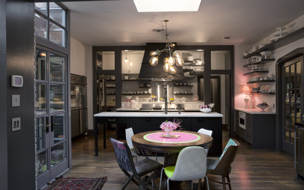 kitchen with steel and glass windows and doors, marble countertops, a french la cornue range, a copper light, shelves on the walls.