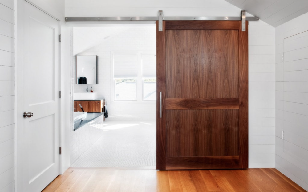 A white bathrooms with modern maples cabinets and a custom barn door hung on stainless hardware