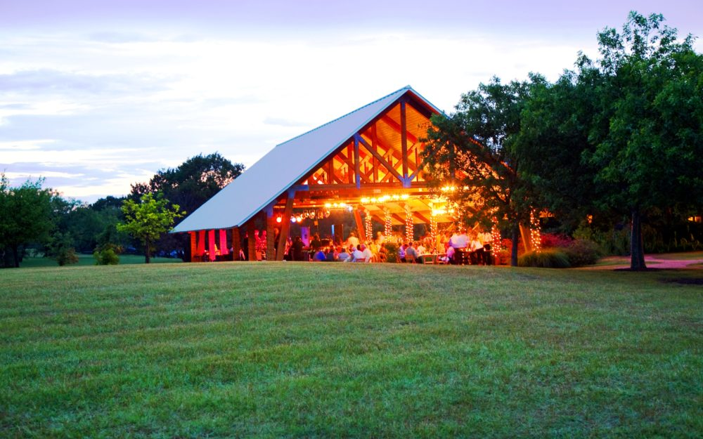 A wooden pavilion decorated for weddings on a green lawn in Texas.